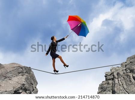 Young businesswoman walking on rope above gap with colorful umbrella - stock photo