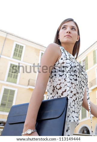 Young businesswoman walking passed classic office buildings in a city square, carrying a black folder.