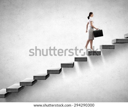 Young businesswoman walking up on staircase representing success concept - stock photo