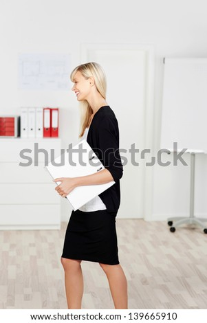 Young businesswoman walking with her laptop on a side view shot - stock photo