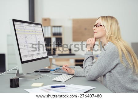 Young businesswoman wearing glasses sitting at her desk in the office working on a desktop computer, side view - stock photo