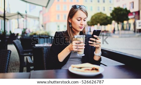 Young Businesswoman wearing Suit using Smartphone in an outdoor Cafe, drinking Coffee. Professional Business Woman texting communicating on the cellphone outdoors. Business City Life