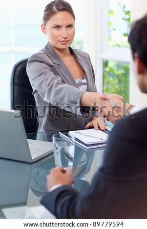 Young businesswoman welcomes customer in her office - stock photo
