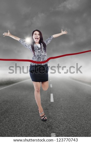 Young businesswoman winning the race with storm clouds background