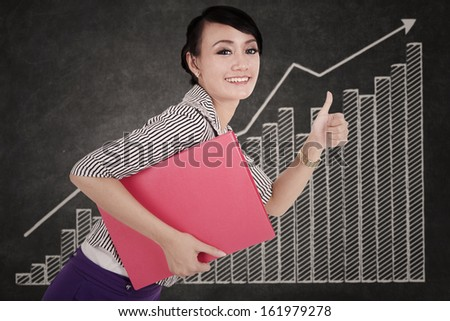 Young businesswoman with a folder showing thumb up against growth graph - stock photo