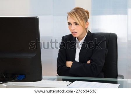 Young Businesswoman With Arm Crossed Looking At Computer In Office - stock photo