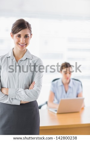 Young businesswoman with arms crossed with colleague working behind - stock photo
