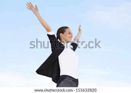 Young businesswoman with arms out against blue sky - stock photo