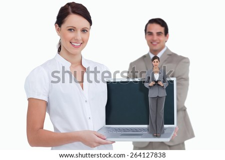 Young businesswoman with binoculars against smiling saleswoman presenting laptop screen with colleague behind her