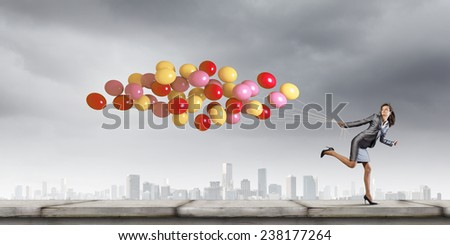 Young businesswoman with bunch of balloons running in a hurry - stock photo