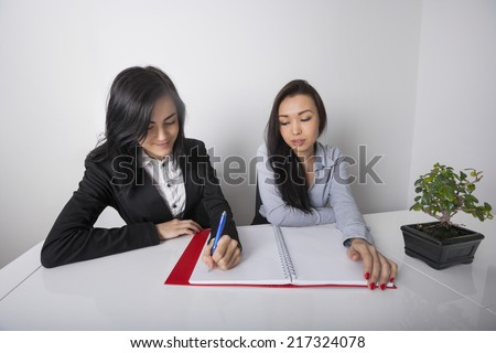 Young businesswoman with colleague writing in spiral notebook at office desk - stock photo