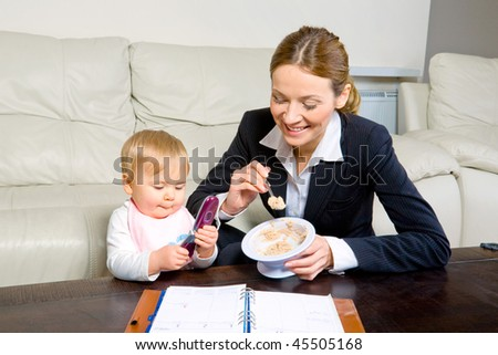 young businesswoman with diary feeding her baby girl