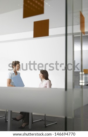 Young businesswoman with file looking at colleague in office - stock photo