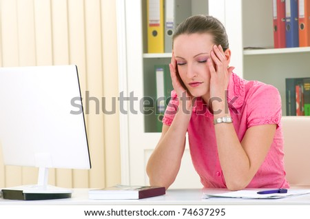 young businesswoman with headache sitting on her desk - stock photo