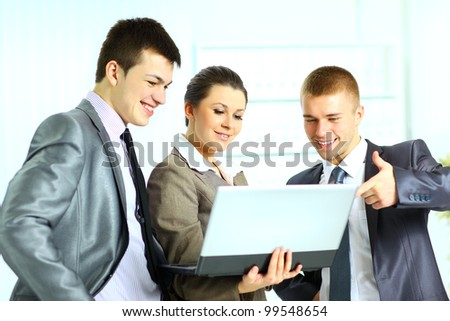 Young businesswoman with her colleagues using laptop - stock photo