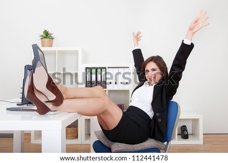 Young Businesswoman With Her Legs On The Desk. - stock photo