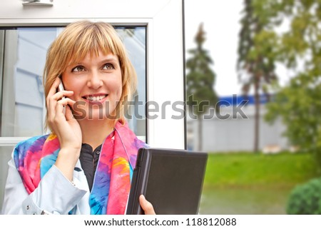 Young businesswoman with laptop and cellphone outdoor - stock photo