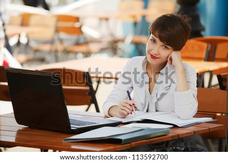 Young businesswoman with laptop at a sidewalk cafe - stock photo