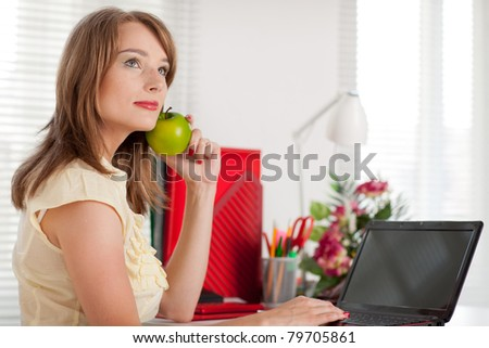 Young businesswoman with laptop sits at the table at the office.