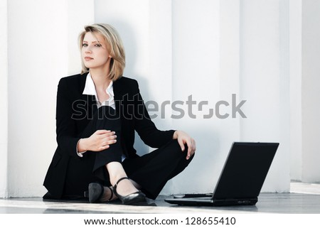 Young businesswoman with laptop sitting on the sidewalk - stock photo