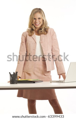 Young businesswoman with laptop standing at desk