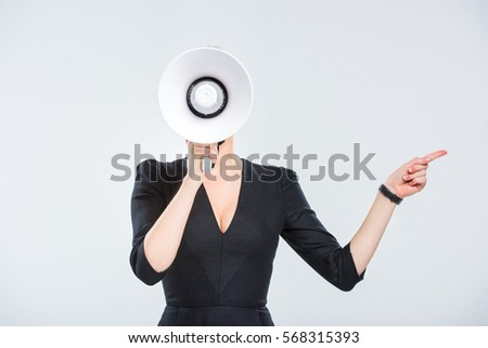 Young businesswoman with megaphone pointing to the side isolated on grey
