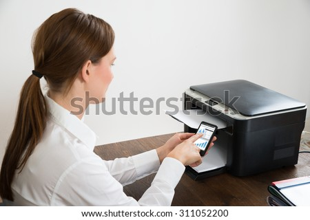 Young Businesswoman With Mobile Phone Showing Graph Connected To Printer At Desk - stock photo