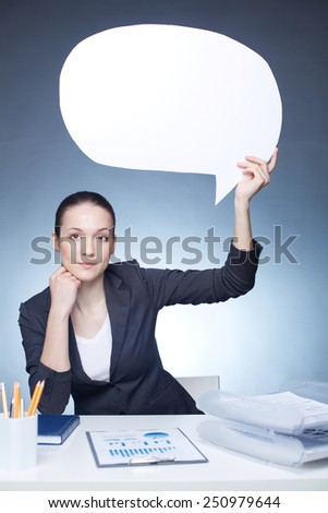 Young businesswoman with paper speech bubble sitting at workplace - stock photo