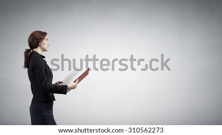 Young businesswoman with red book in hands