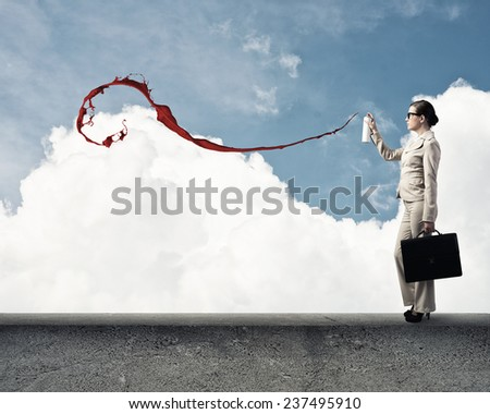 Young businesswoman with suitcase using spray balloon - stock photo