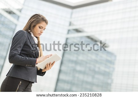 Young businesswoman with tablet in front of office building - stock photo