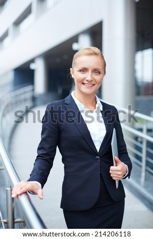 Young businesswoman with touchpad looking at camera - stock photo