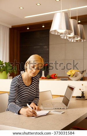 Young businesswoman working at home, sitting at table, having laptop . - stock photo