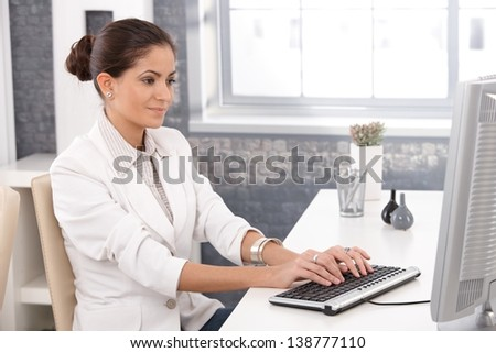 Young businesswoman working at office desk, typing on keyboard, smiling.