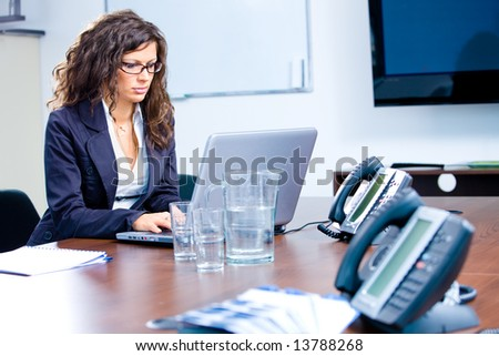 Young businesswoman working on laptop computer at office in meeting room.
