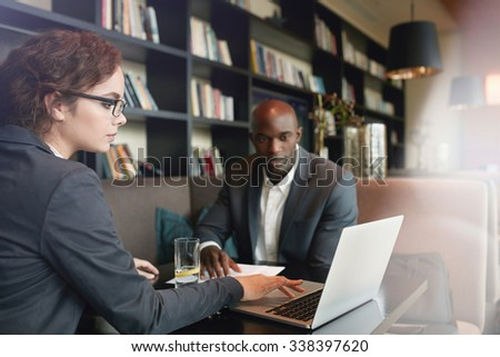 Young businesswoman working on laptop with her business partner while sitting at cafe. Young executives at coffee shop meeting for new business discussions. - stock photo