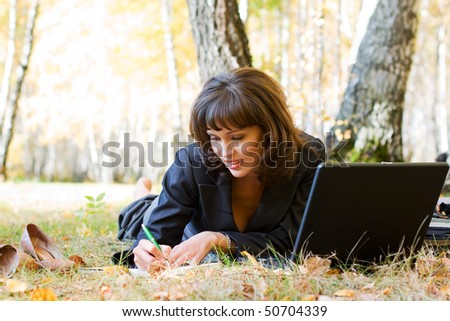Young businesswoman working on nature. - stock photo