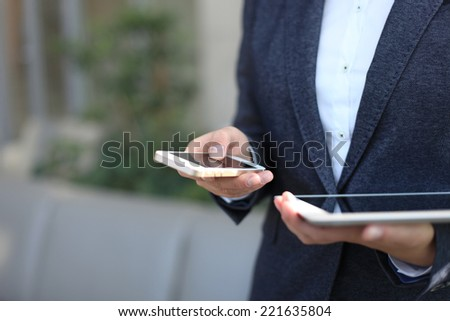 Young businesswoman working with modern devices, digital tablet computer and mobile phone - stock photo