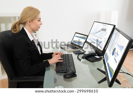 Young Businesswoman Working With Statistics Data On Computer At Glass Desk - stock photo