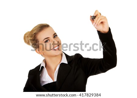 Young businesswoman writes something with big pen - stock photo