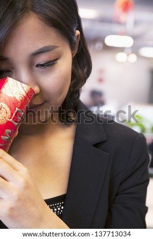 Young businesswomen looking into traditional red envelopment, Chinese New Year - stock photo