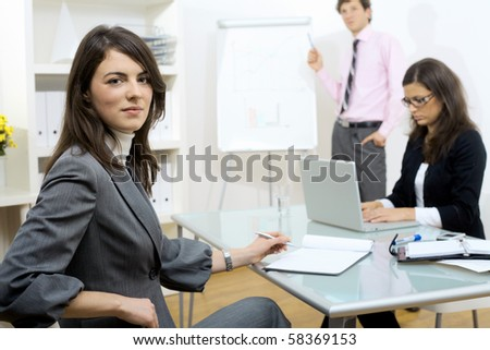 Young businesswomen sitting at desk, writing notes. Businesswoman standing in background, drawing chart on whiteboard. Selective focus on woman in front. - stock photo