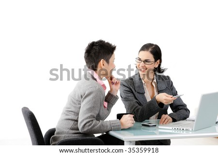 Young businesswomen sitting at office desk, looking at each other, smiling. Isolated on white. - stock photo