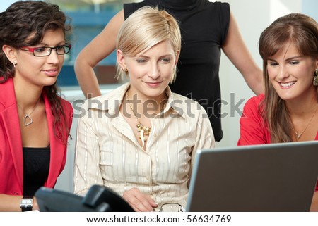 Young businesswomen sitting at table in meeting room, using laptop computer, smiling. - stock photo