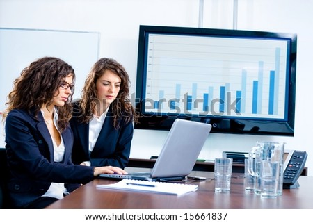 Young businesswomen sitting by meeting table at office in front of a huge blank plasma TV screen and using laptop and phone. - stock photo