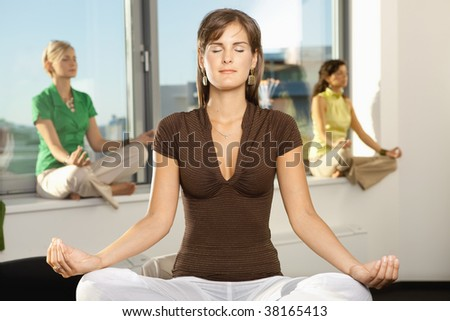 Young businesswomen sitting in yoga position in office. - stock photo
