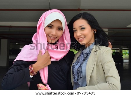 Young businesswomen smile in parking - stock photo