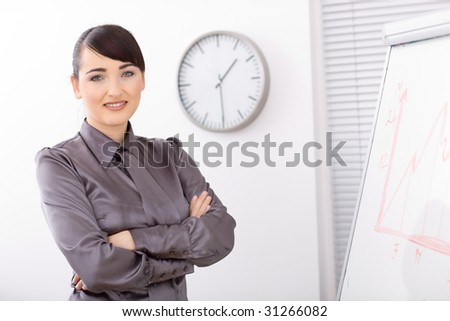 Young businesswomen standing arms crossed besides a whiteboard, smiling. - stock photo