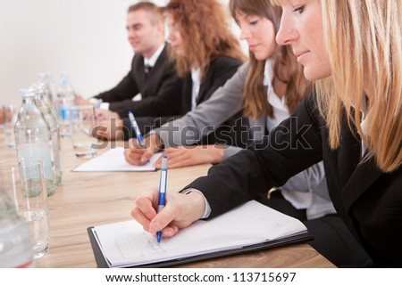 Young Businesswomen Taking Note In Meeting With Colleagues