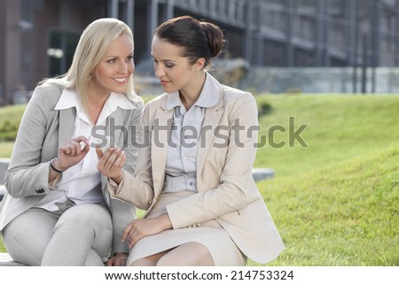 Young businesswomen with mobile phone sitting against office building - stock photo